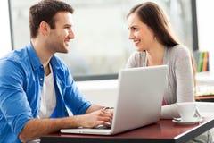 Paare, die Laptop am Café sprechen und verwenden Stockfotografie