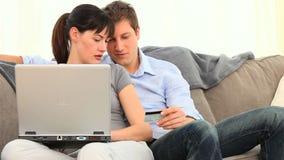 Junge Paare unter Verwendung einer Kreditkarte, zum auf Internet zu zahlen stock video footage