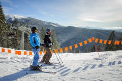 Junge Paare von den Frauen, die Ski fahrend am Skiort genießen lizenzfreies stockbild