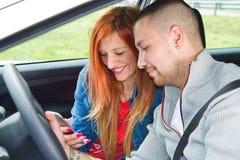 Junge Paare von den lächelnden Leuten, die zum Handy schauen Lizenzfreie Stockfotografie