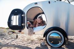 Junge Paare von den Reisenden, die in der Natur liegt in ihrem Wohnmobil kühlen lizenzfreie stockfotografie