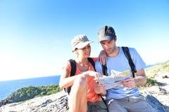 Junge Paare von den Wanderern, welche die Karte sitzt auf einem Felsen durch das Meer betrachten Stockfotografie