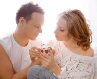 Junge Paare von Liebhabern. Mann stellt Blume dar stockbild