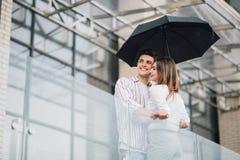 Junge Paare von Liebhabern unter einem Regenschirm in der Stadt Hübsche Leute, die Spaß in Stadtstadtzentrum an einem regnenden T lizenzfreie stockbilder