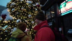Junge Paare von Skifahrern stehen nahe dem Weihnachtsbaum draußen Reflexion des Weihnachtslichtes in den Gläsern stock footage