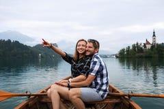 Junge Paare von Touristen auf hölzernem Boot auf dem See bluteten, Slowenien Stockbild