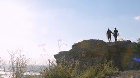 Junge Paare von Touristen klettern zur Spitze des Berges stock video
