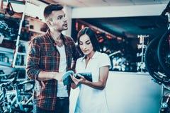 Junge Paare wählen Fahrrad betrachten Katalog im Geschäft lizenzfreie stockbilder