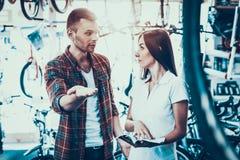Junge Paare wählen Fahrrad betrachten Katalog im Geschäft lizenzfreies stockbild