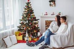 Junge Paare am Weihnachtsbaum Stockbilder