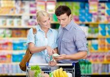 Junge Paare, welche die Einkaufsliste und die ausgesuchten Produkte besprechen lizenzfreie stockfotos