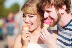 Junge Paare, welche die Eiscreme im Freien essen Lizenzfreie Stockbilder