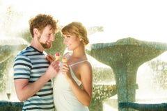 Junge Paare, welche die Eiscreme im Freien essen Stockfotografie