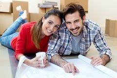 Junge Paare, welche die Pläne ihres neuen Hauses betrachten Lizenzfreie Stockfotos
