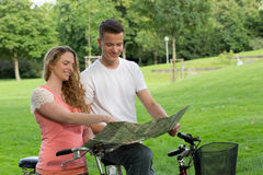 Junge Paare, welche die Richtung während einer Fahrradreise suchen Lizenzfreie Stockbilder