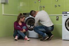 Junge Paare, welche die Waschmaschine im Raum laden Lizenzfreies Stockfoto