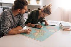 Junge Paare, welche die Weltkarte erforschen Stockbilder