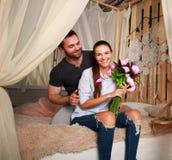 Junge Paare zu Hause auf Bett mit Blumenstrauß von Blumen Lizenzfreies Stockbild