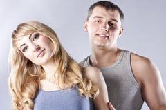 Junge Paare zusammen auf grauem Hintergrund Stockfotografie