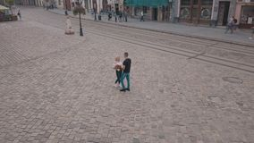 Junge Paare zusammen in der Mitte der Straße Mann mit einem Blumenstrauß der Blumen Schießen von der Luft stock video