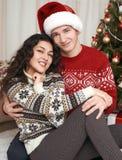 Junge Paare zusammen mit Weihnachtsbaum im Hauptinnenraum - Liebes- und Feiertagskonzept, Weihnachtsvorabend Lizenzfreies Stockfoto