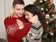 Junge Paare zusammen mit Weihnachtsbaum im Hauptinnenraum - Liebes- und Feiertagskonzept, Weihnachtsvorabend Lizenzfreie Stockfotografie