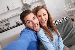 Junge Paare zusammen weekend zu Hause, selfie Zunge herausnehmend Stockfotos