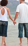 Junge Paarholdinghände auf dem Strand Lizenzfreies Stockbild
