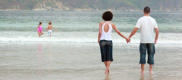 Junge Paarholdinghände auf dem Strand Stockfotos