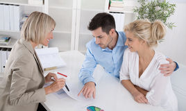 Junge Paarkunden und Berater oder Vertreter, die über financ sprechen Stockbilder
