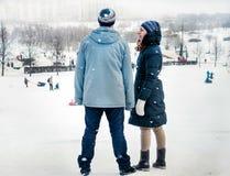 Junge Paarmann- und -frauenstellung gegen Winterlandschaft lizenzfreie stockbilder