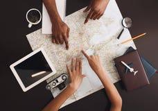 Junge Paarplanungs-Flitterwochenurlaubsreise mit Karte lizenzfreie stockfotos