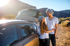 Junge Paarreisende, die Spaß nahe dem Auto haben stockfotografie