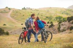 Junge Paarreitfahrräder in den Bergen stockfotos