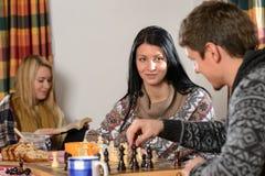 Junge Paarspielschachwinter-Häuschenlandschaft Stockbilder