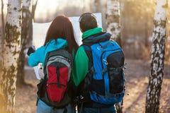 Junge Paarwanderer, die Karte betrachten Stockbild