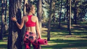 Junge passten athletische Frau in einem Wald, der intelligente Uhr trägt und Yogamatte hält Verstand und Körperkonzept mit Kopien Lizenzfreie Stockfotografie