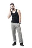 Junge passten den bärtigen Mann in der Sportkleidung lächelnd und am Handy sprechend Stockbild