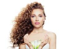 Junge perfekte Frau mit langer gelockter Frisur, gesunder Haut und Lilienblume in ihren Händen lokalisiert auf weißem Hintergrund lizenzfreies stockbild