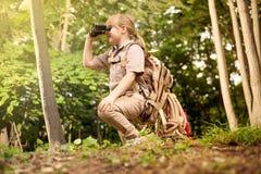 Junge Pfadfinderin, erforscht Natur mit Ferngläsern auf kampierendem tr stockfotos