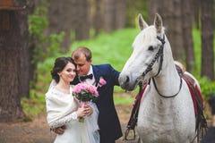 Junge pflegen sich und Braut mit Pferd im Park Lizenzfreies Stockbild
