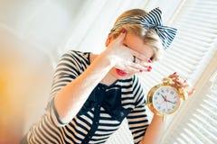 Junge Pinupfrau, die Wecker zeigt und Gesicht versteckt Stockbild