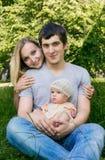 Junge positive Familie mit kleiner Tochter draußen Lizenzfreie Stockbilder