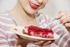Junge positive Frau schmeckt ein Stück Käsekuchen mit raspb Stockbild