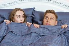 Junge positive liebevolle Paare unter Decke im Bett und Untersuchung Augen stockfoto