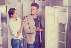 Junge positive Paare, die neuen Kühlschrank im Grossmarkt wählen Lizenzfreies Stockfoto