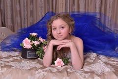 Junge Prinzessin in einem blauen Abendkleid mit Rosen Stockfotos