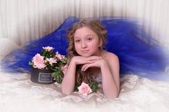 Junge Prinzessin in einem blauen Abendkleid mit Rosen Lizenzfreie Stockfotografie