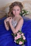 junge Prinzessin in einem blauen Kleid sitzt mit einem Blumenstrauß von ROS Stockbilder
