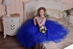 junge Prinzessin in einem blauen Kleid sitzt mit einem Blumenstrauß von ROS Lizenzfreie Stockfotografie